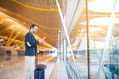 Uomo che per mezzo del telefono cellulare all'aeroporto che guarda depressione la finestra fotografie stock libere da diritti