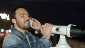 Uomo che per mezzo del telefono cellulare e esaminando uno spettatore della torre Fotografia Stock Libera da Diritti
