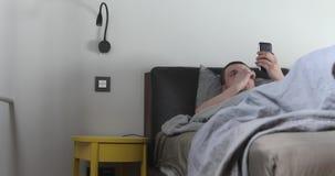 Uomo che per mezzo del telefono cellulare a letto stock footage