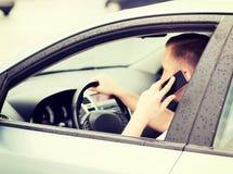 Uomo che per mezzo del telefono mentre conducendo l'automobile Fotografie Stock
