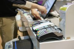 Uomo che per mezzo del terminale di posizione al negozio che paga la carta di credito il purch Immagini Stock Libere da Diritti