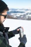 Uomo che per mezzo del termos dentro su una montagna nevosa Immagini Stock Libere da Diritti