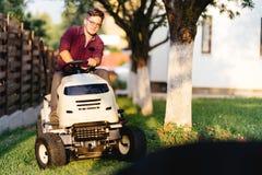 uomo che per mezzo del trattore del prato inglese e tagliando erba nel giardino durante il tempo di fine settimana Immagine Stock Libera da Diritti