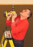 Uomo che per mezzo del trivello per installare illuminazione della pista Fotografia Stock Libera da Diritti