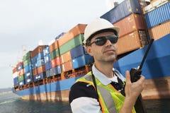 Uomo che per mezzo del walkie-talkie al terminale di contenitore Fotografie Stock Libere da Diritti
