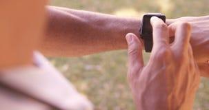 Uomo che per mezzo dell'orologio astuto archivi video