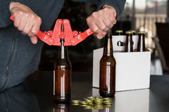 Uomo che per mezzo della capsulatrice per mettere i cappucci del metallo sulla bottiglia di birra Immagine Stock Libera da Diritti
