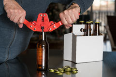 Uomo che per mezzo della capsulatrice per mettere i cappucci del metallo sulla bottiglia di birra Immagini Stock