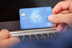 Uomo che per mezzo della carta di credito e del computer portatile per comperare online Immagini Stock