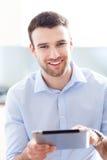 Uomo che per mezzo della compressa digitale Immagine Stock