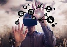 Uomo che per mezzo della cuffia avricolare di realtà virtuale con le icone dell'applicazione contro il paesaggio urbano Fotografie Stock