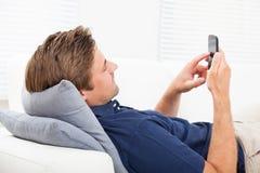 Uomo che per mezzo dello Smart Phone sul sofà Fotografia Stock Libera da Diritti