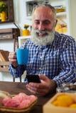 Uomo che per mezzo dello smartphone e tenendo un tè del caffè che si siede alla linguetta Fotografia Stock