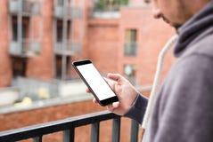 Uomo che per mezzo dello smartphone mobile moderno Sparato con il punto di vista della terza persona, schermo in bianco fotografia stock libera da diritti