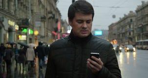 Uomo che per mezzo dello smartphone sulla via stock footage