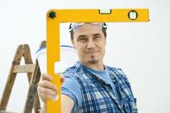 Uomo che per mezzo dello strumento livellato Fotografia Stock Libera da Diritti