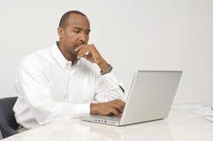 Uomo che per mezzo di un computer portatile Fotografia Stock