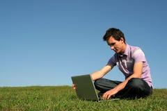 Uomo che per mezzo di un computer portatile all'aperto Fotografia Stock Libera da Diritti