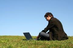 Uomo che per mezzo di un computer portatile all'aperto Immagini Stock Libere da Diritti