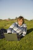 Uomo che per mezzo di un computer portatile all'aperto Fotografia Stock