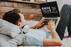 Uomo che per mezzo di un computer portatile per comprare in un web dello speciale di acquisto di Black Friday Fotografia Stock Libera da Diritti