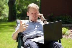 Uomo che per mezzo di un computer portatile e parlando sul telefono Immagini Stock Libere da Diritti