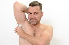 Uomo che per mezzo di un deodorante Fotografia Stock Libera da Diritti