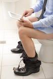 Uomo che per mezzo di un PC della compressa mentre sedendosi sulla toilette. Immagini Stock Libere da Diritti