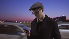 Uomo che per mezzo di un telefono mobile Un uomo sta sulla via vicino alla strada con passare le automobili video d archivio