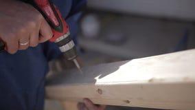 Uomo che per mezzo di un trapano d'acciaio e di un cacciavite usuale sul piatto di legno stock footage