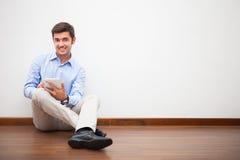 Uomo che per mezzo di una compressa digitale Fotografie Stock