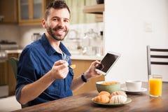 Uomo che per mezzo di una compressa sopra la prima colazione fotografia stock libera da diritti