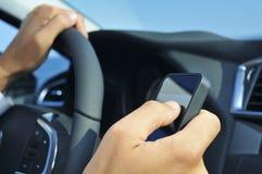 Uomo che per mezzo di uno smartphone mentre conducendo un'automobile Fotografia Stock Libera da Diritti