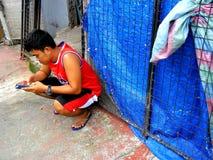 Uomo che per mezzo di uno smartphone mentre sedendosi su un marciapiede Immagine Stock