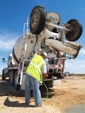 Uomo che perde tempo con il tubo flessibile sul camion del cemento - verticale Fotografia Stock