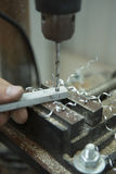 Uomo che perfora dentro piatto d'acciaio con il trapano del banco Primo piano elettrico Fotografie Stock