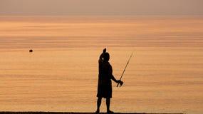 Uomo che pesca da solo nel mare all'alba o al tramonto immagini stock libere da diritti