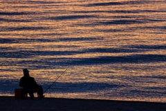 Uomo che pesca da solo nel mare all'alba o al tramonto Fotografie Stock Libere da Diritti