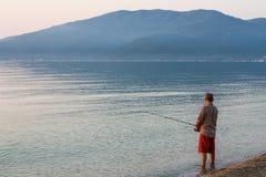 Uomo che pesca da solo nel mare molto nelle prime ore del mattino - a Sunr Fotografie Stock