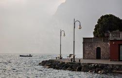 Uomo che pesca vicino alla riva di polizia del lago Immagini Stock Libere da Diritti