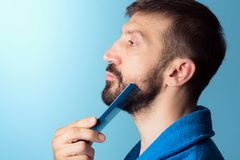 Uomo che pettina barba fotografia stock