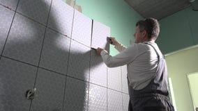 Uomo che piastrella bagno Piastrelle di ceramica di disposizione del lavoratore qualificato stock footage