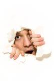 Uomo che pigola attraverso il foro su documento fotografia stock