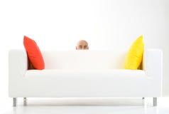 Uomo che pigola da dietro il sofà Fotografie Stock Libere da Diritti