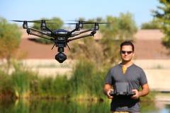 Uomo che pilota un fuco alta tecnologia della macchina fotografica Fotografie Stock Libere da Diritti