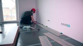 Uomo che pone pavimentazione laminata nella costruzione video d archivio