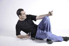 Uomo che pone sul pavimento e sull'indicare Fotografia Stock