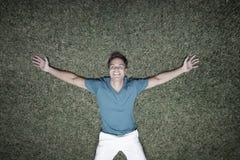 Uomo che pone sull'erba Immagini Stock Libere da Diritti