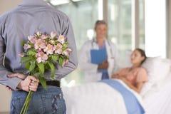 Uomo che porta i fiori al paziente Fotografia Stock