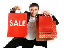 Uomo che porta i sacchetti della spesa rossi di vendita fotografie stock